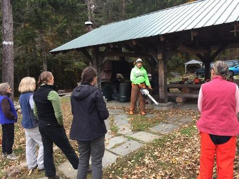 tish carr demonstrating the proper technique for starting a chainsaw. carr and Amanda Mahaffey led a Women's Chainsaw Safety Training at Yale-Myers in October 2019, put on by QCI and the Forest Stewards Guild.