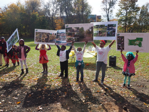 Children of Cherry Ann Park hold up signs of projects underway, including the splash pad.